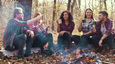 Young hikers toasting with thermo mugs by campfire in autumn forest