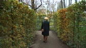 doolhof : Girl walking between rows of trees in garden labyrinth in autumn