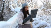 backlit : Beautiful happy woman typing on the tablet. Snow covered trees in winter park.