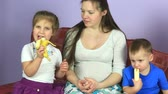 sister : Pregnant woman with young children eating bananas. Happy family waiting for third child. Stock Footage