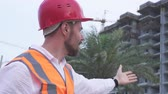 mimar : Man in a helmet, architect, engineer, manager tells about the progress of construction in the evening stock footage video