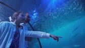 живой : Teenage girl with Dad watching the fish in the Aquarium stock footage video