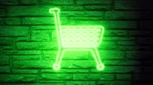 купон : Green shopping cart neon blink on brick background. Shopping, offer, discount background.