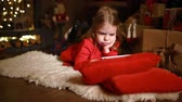 atmosfera : Little girl lying in carpet with presents around using tablet on red pillow.