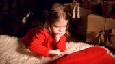 prezent : Little girl lying in carpet with presents around using tablet on