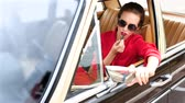 aplicar : Beautiful woman in black sunglasses sitting in the retro car and doing make-up Stock Footage