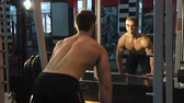 violência : Young athletic man doing exercise in gym. Shallow depth of field. Back pull in gym machine