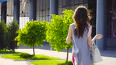 black hair : Lady With Handbag Comes Near Business Center. Slow motion. Stock Footage