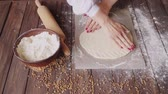 dough : Woman rolling out dough on a cutting board on the wooden table full of flour on the kitchen at home while making pasta
