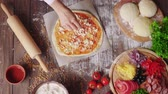 pizza cheese : Close up of Woman Puts cheese on the dough while making pizza in the kitchen Stock Footage