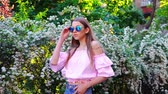 arbusto : Teenager girl in pink shirt, blue jeans and sunglasses walking near the flowering bush at sunset and look up to the sky.