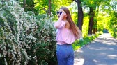 vegetação : Teenager girl in pink shirt, blue jeans and sunglasses walking near the flowering bush at sunset, turned back to see and go away.