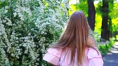 arbusto : Teenager girl in pink shirt, blue jeans and sunglasses walking near the flowering bush at sunset, turned back to see and go away.