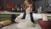 dough : Kneading the dough on the table full of flour. Footage of a beautiful liithe 5 years old girl kneading the dough on the wooden table full of flour on the kitchen at home.