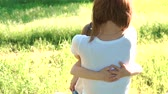 Daughter rushes into mothers arms and gives her a big hug. Outside in the park. Sunset. Slow motion.
