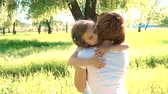 contato : Daughter rushes into mothers arms and gives her a big hug. Outside in the park. Sunset. Slow motion.