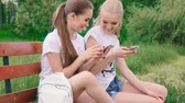 Happy girlfriends with smartphone in the park