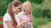 drby : Happy girlfriends with smartphone in the park