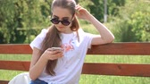 mensagem : Girl talking on the smart phone sitting in a park on wood bench with green tree leaf, Nature scene
