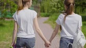 desportivo : attractive girls walking through the Park and smile. girlfriends spend time together outdoor. slow motion
