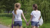 attractive girls walking through the Park and smile. girlfriends spend time together outdoor. slow motion