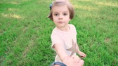 Adorable little girl smiling and holding hand of parent on meadow