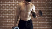 Concentrated topless bodybuilder doing exercise on biceps with dumbbells over brick wall background. 影像素材
