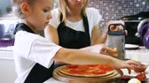 pizza cheese : Young woman wuth her little adorable daughter in formal clothing making pizza in modern kitchen at home.