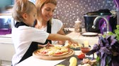slices : Young woman wuth her little adorable daughter in formal clothing making pizza in modern kitchen at home.