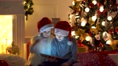 lareira : Excited boy and girl sitting near Christmas tree, playing tablet game together. Stock Footage