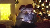 уютный : Excited boy and girl sitting near Christmas tree, playing tablet game together. Стоковые видеозаписи