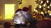гаджет : Excited boy and girl sitting near Christmas tree, playing tablet game together. Стоковые видеозаписи
