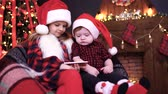 sorella : Two children, boy and girl in Christmas decorations playing smartphone