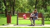 anyaság : Mother and little daughter in outdoors public park sitting on the bench and read book, study lessons. Parenthood and child concept. Mother kissing her child.