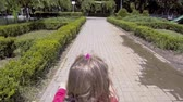 bike ride : Happy little girl riding a bicycle. Close up, shoulder view Stock Footage