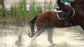 Rider with horse crossing water jump galloping at a cross country manisfestation. Slow motion