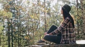 Dreaming woman on rock in woods Stock Footage