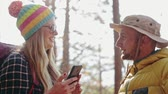 Pretty traveling woman and hansome man are standing on top of mountain Stock Footage