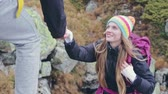 与え : Pretty woman backpacker hiking in the mountains being given a helping hand from above by her smiling boyfriend