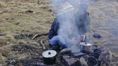 Young couple cooking over a campfire while out hiking laughing and chatting obscured by smoke