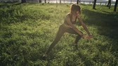 magro : Young woman exercising outdoors stretching one of her legs Vídeos