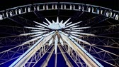 counterclockwise : Rotating illuminated ferris wheel from below with passenger gondolas suspended on the rim against a night sky at a carnival or funfair. Stock Footage