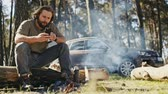 strong tea : Muscular casual man sitting with axe at burning campfire in forest and using phone on background of car.