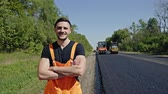 kombinace : Man in overalls standing alongside a tarred road