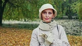 unemotional : Fashionable elderly lady in an elegant autumn outfit standing outdoors in a park looking thoughtfully at the camera as in pans around her