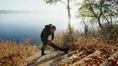 hajlik : Young guy in sportswear doing warming up exercise while standing on stairs near calm lake on sunny autumn day