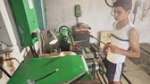 öğrenme : Male teenager in casual outfit taking metal tool from lathe while standing in professional workshop Stok Video