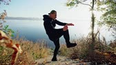 focused : Handsome young guy standing in fighting stance and performing exercises while standing on steps near lake on sunny autumn day. Stock Footage