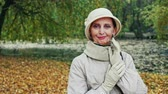 аксессуар : Senior woman posing for camera in autumn park