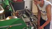 leviers : Teenager examining lathe in workshop